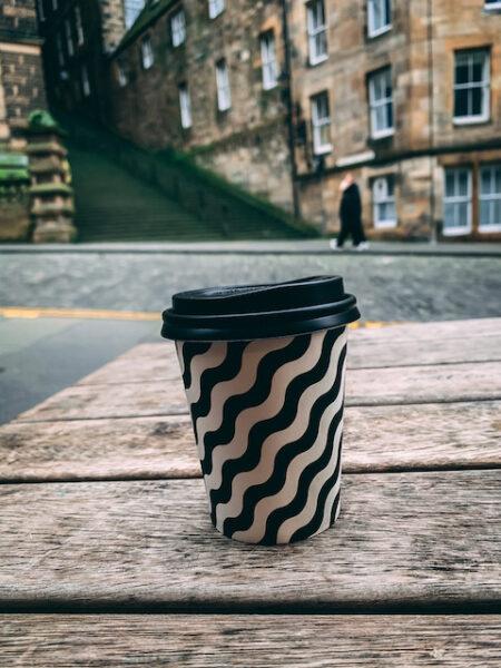 Striped takeaway Coffee Cup on table outside The Milkman Coffee Shop- Emma Inks Edinburgh Coffee Shop Blog Post